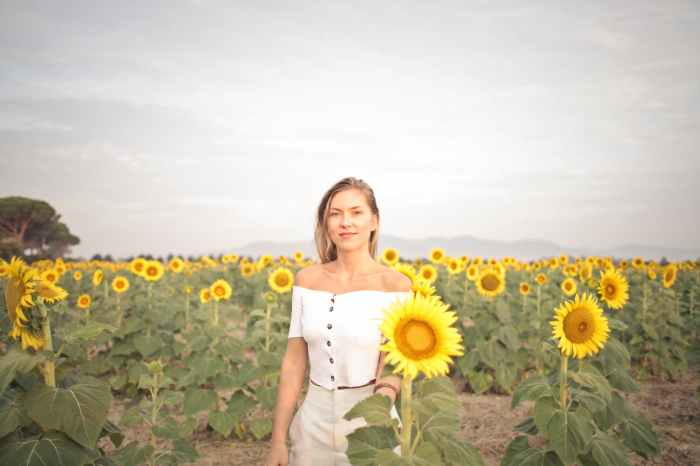 photo of a woman standing on the sunflower field