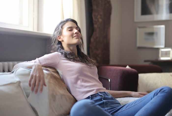 photo of woman in pink long sleeve shirt and blue denim jeans sitting on brown sofa with her eyes closed