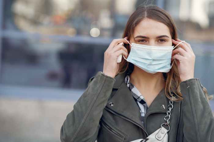woman in gray coat wearing white face mask