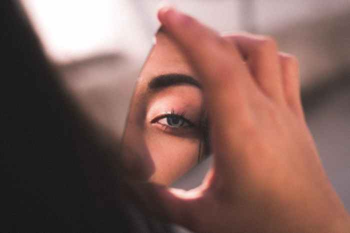 reflection of woman s eye on broken mirror